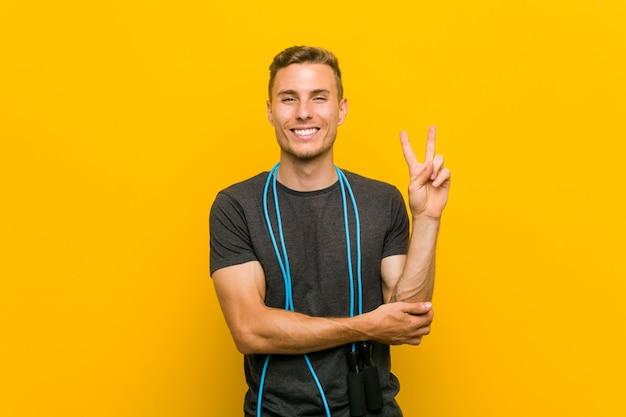Hombre caucásico joven que sostiene una comba que muestra el número dos con los dedos.