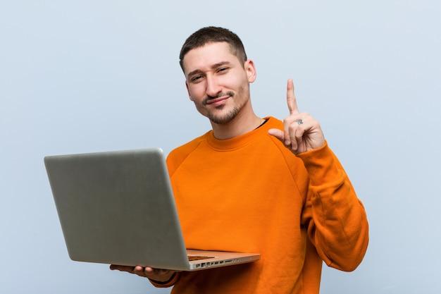 Hombre caucásico joven que sostiene una computadora portátil que muestra el número uno con el dedo.