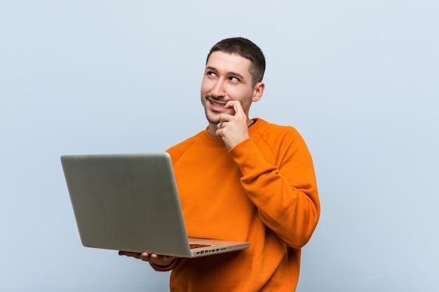 Hombre caucásico joven que sostiene una computadora portátil relajada pensando en algo que mira un espacio de la copia.
