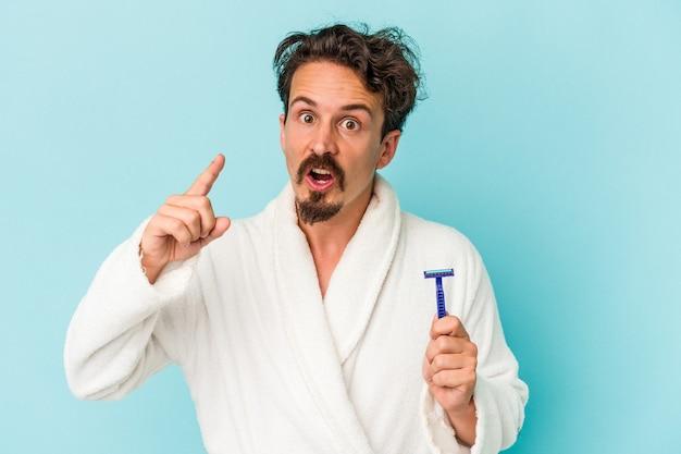 Hombre caucásico joven que sostiene una hoja de afeitar aislada sobre fondo azul que tiene una idea, concepto de inspiración.
