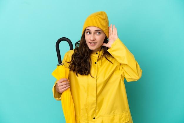 Hombre caucásico joven que sostiene un paraguas aislado sobre fondo azul escuchando algo poniendo la mano en la oreja