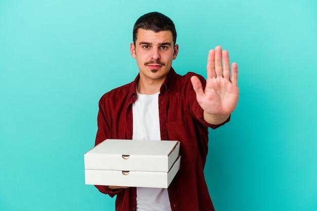 Hombre caucásico joven que sostiene las pizzas aisladas en azul que se coloca con la mano extendida que muestra la señal de pare, que le impide.