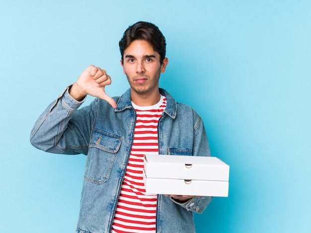Hombre caucásico joven que sostiene las pizzas aisladas que muestran un gesto de la aversión, pulgares abajo. concepto de desacuerdo