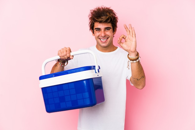 Hombre caucásico joven que sostiene un refrigerador portátil alegre y confiado que muestra gesto aceptable.
