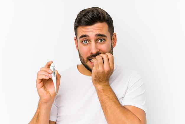 Hombre caucásico joven que sostiene un termómetro aislado hombre caucásico joven que sostiene morderse las uñas, nervioso y muy ansioso.