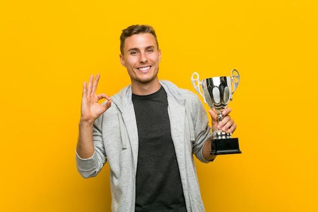Hombre caucásico joven que sostiene un trofeo alegre y confiado que muestra gesto aceptable.