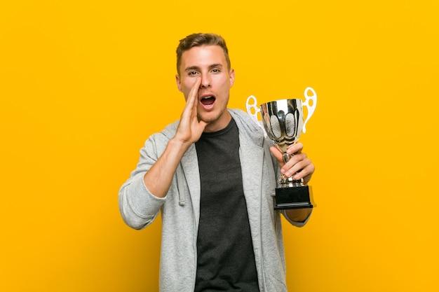Hombre caucásico joven que sostiene un trofeo gritando emocionado al frente.