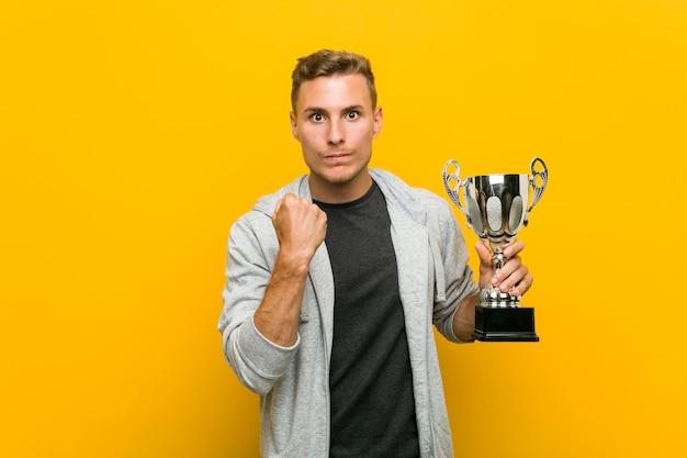 Hombre caucásico joven que sostiene un trofeo que muestra el puño a la cámara, expresión facial agresiva.