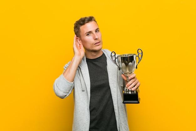 Hombre caucásico joven que sostiene un trofeo tratando de escuchar un chisme.