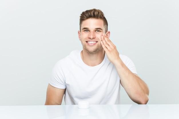 Hombre caucásico joven que usa la crema hidratante facial