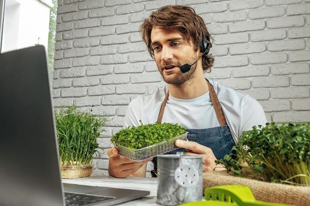 Hombre caucásico joven que vende micro brotes verdes en línea