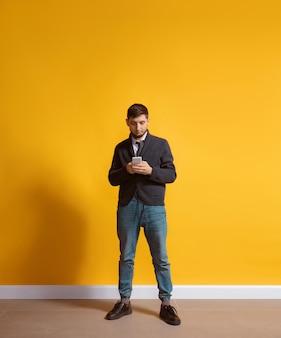 Hombre caucásico joven con retrato de cuerpo entero de smartphone aislado sobre pared amarilla