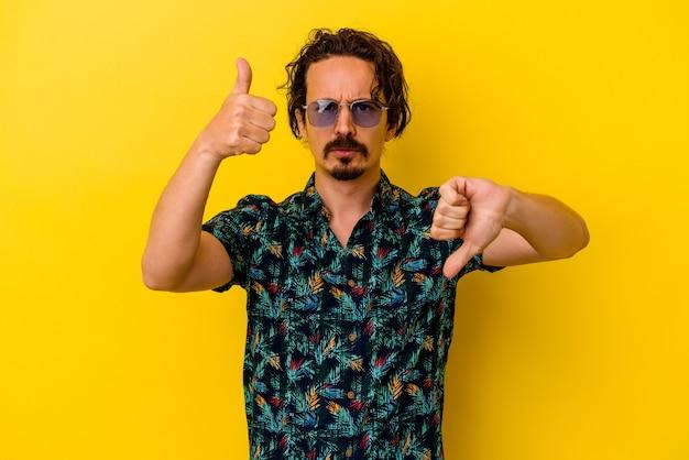 Hombre caucásico joven con ropa de verano aislado sobre fondo amarillo que muestra los pulgares hacia arriba y hacia abajo, concepto difícil de elegir