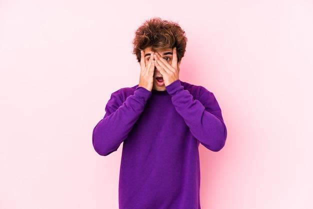 Hombre caucásico joven en rosa aislado parpadeo a través de los dedos asustado y nervioso.
