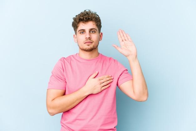Hombre caucásico joven rubio de pelo rizado aislado haciendo un juramento, poniendo la mano en el pecho.