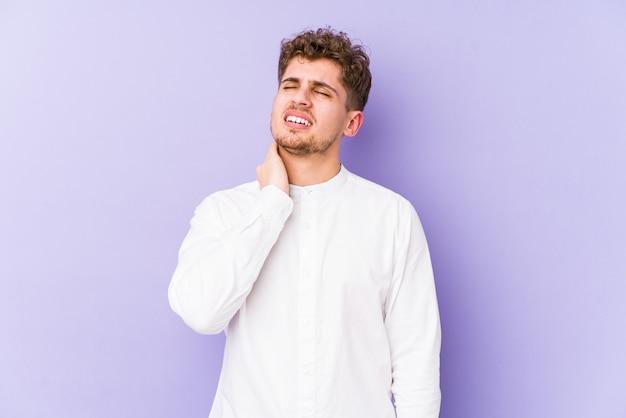 Hombre caucásico joven rubio del pelo rizado aislado que tiene un dolor de cuello debido al estrés, masajeándolo y tocándolo con la mano.
