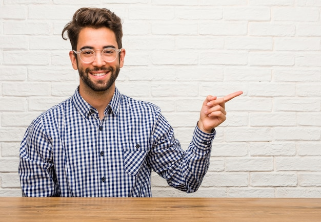 Hombre caucásico joven sentado apuntando hacia el lado, sonriendo sorprendido presentando algo, natural y casual