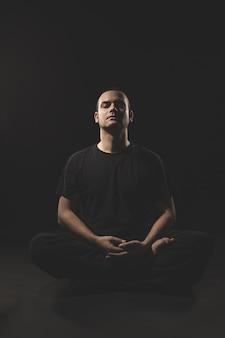 Hombre caucásico joven sentado en meditación con ropa negra y negra