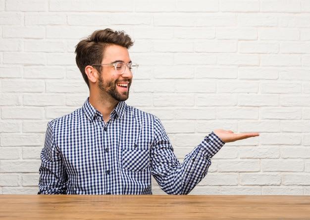 Hombre caucásico joven sentado sosteniendo algo con las manos, mostrando un producto, sonriente y alegre, ofreciendo un objeto imaginario