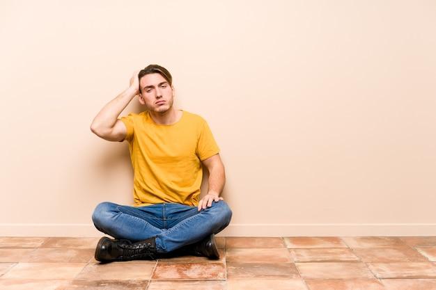 Hombre caucásico joven sentado en el suelo aislado cansado y muy somnoliento manteniendo la mano en la cabeza.