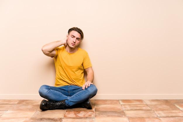 Hombre caucásico joven sentado en el suelo aislado sufriendo dolor de cuello debido al estilo de vida sedentario.