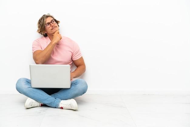 Hombre caucásico joven sentado en el suelo con su computadora portátil aislado en blanco y mirando hacia arriba