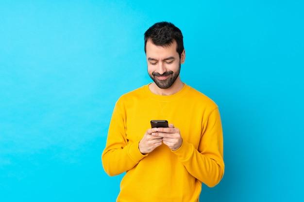 Hombre caucásico joven sobre la pared azul aislada que envía un mensaje con el móvil