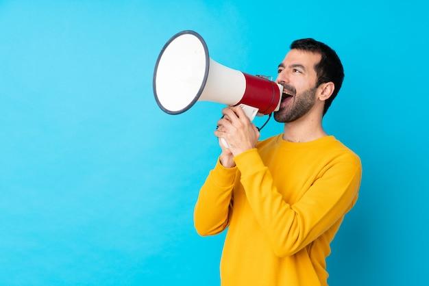 Hombre caucásico joven sobre la pared azul aislada que grita a través de un megáfono