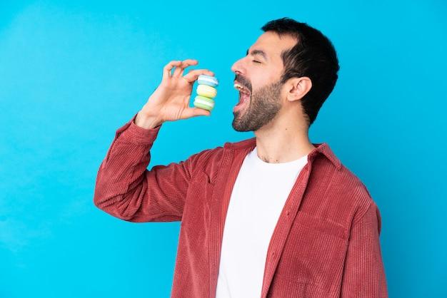 Hombre caucásico joven sobre la pared azul aislada que sostiene los macarons franceses coloridos y que lo come