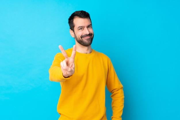 Hombre caucásico joven sobre pared azul aislado sonriendo y mostrando el signo de la victoria