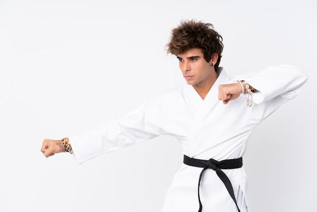 Hombre caucásico joven sobre la pared blanca aislada que hace karate