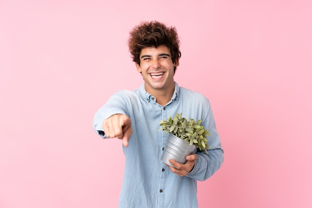 Hombre caucásico joven sobre la pared rosada aislada que toma una maceta y que señala al frente