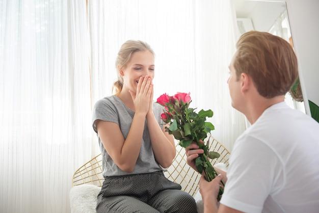 El hombre caucásico joven sorprende a la novia con el manojo de rosa para celebrar su día de boda del aniversario. el par tiene tiempo feliz junto en casa. concepto del día de san valentín.