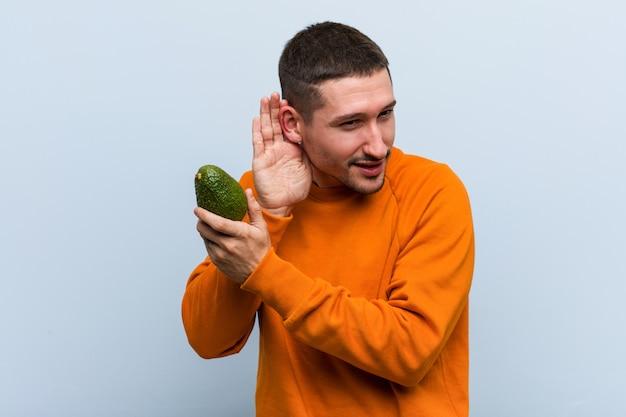 Hombre caucásico joven sosteniendo un aguacate tratando de escuchar un chisme.