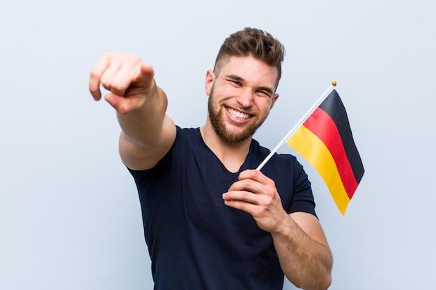 Hombre caucásico joven sosteniendo una bandera de alemania sonrisas alegres apuntando al frente.