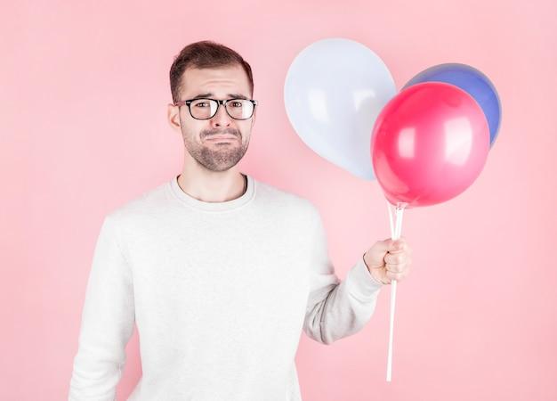 Hombre caucásico joven sosteniendo globos con expresión facial muy molesta y celebrando el cumpleaños en la pared rosa, nadie vino
