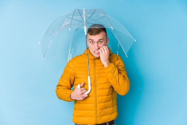 Hombre caucásico joven sosteniendo un paraguas morderse las uñas, nervioso y muy ansioso.