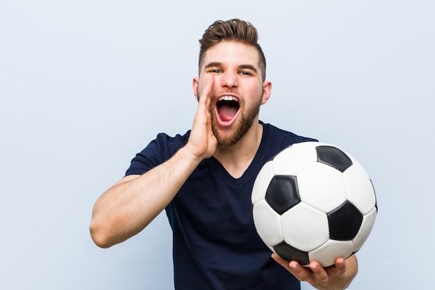 Hombre caucásico joven sosteniendo una pelota de fútbol gritando emocionado al frente.