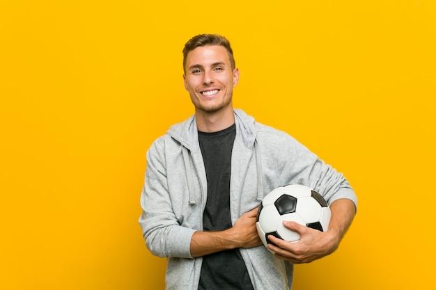 Hombre caucásico joven sosteniendo una pelota de fútbol sonriendo confiados con los brazos cruzados.