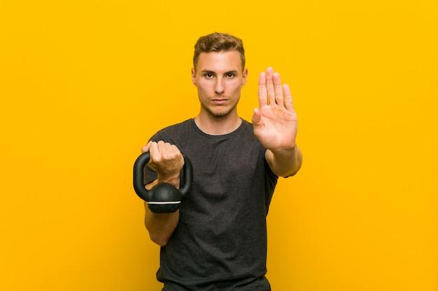 Hombre caucásico joven sosteniendo una pesa de pie con la mano extendida que muestra la señal de stop, impidiéndole.
