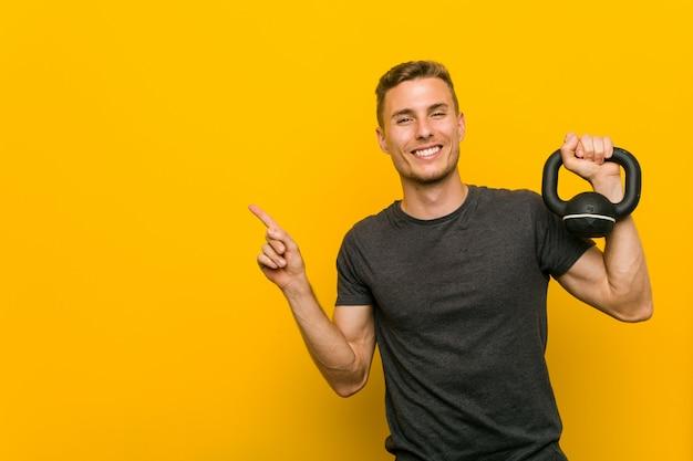 Hombre caucásico joven sosteniendo una pesa sonriendo alegremente señalando con el dedo de distancia.
