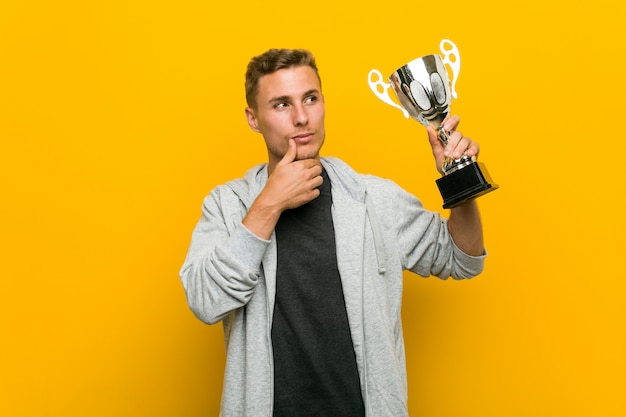 Hombre caucásico joven sosteniendo un trofeo mirando hacia los lados con expresión dudosa y escéptica.