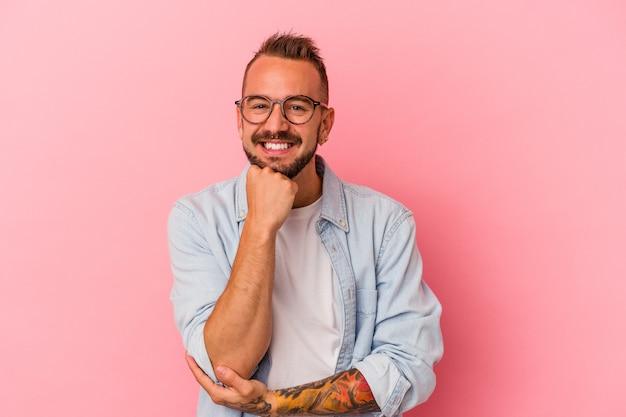 Hombre caucásico joven con tatuajes aislados sobre fondo rosa sonriendo feliz y confiado, tocando la barbilla con la mano.