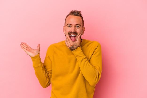Hombre caucásico joven con tatuajes aislados sobre fondo rosa tiene espacio de copia en una palma, mantenga la mano sobre la mejilla. asombrado y encantado.