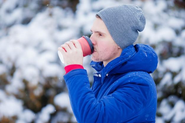 Hombre caucásico joven tomando café en invierno congelado día al aire libre