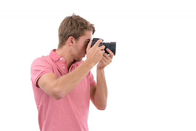 Hombre caucásico joven tomando fotos con cámara de fotos en aislado