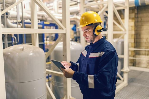 Hombre caucásico joven en traje protector usando tableta mientras está de pie en la planta de calefacción.