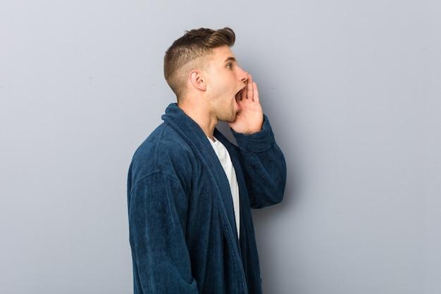 Hombre caucásico joven vistiendo pijama gritando y sosteniendo la palma cerca de la boca abierta.