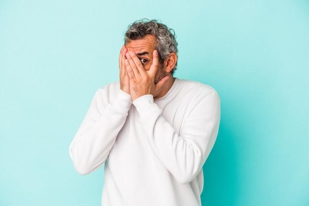 Hombre caucásico de mediana edad aislado sobre fondo azul parpadear a través de los dedos asustado y nervioso.