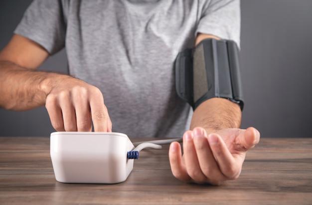 Hombre caucásico midiendo su presión arterial en casa.